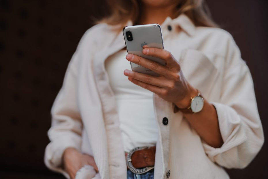 woman in white coat holding silver iphone 6